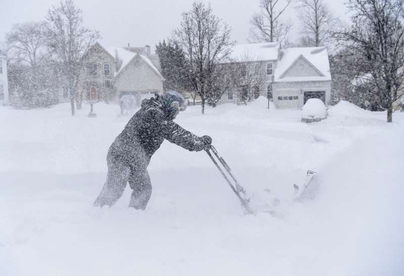 Jocelyn McCoy plows out her neighbors as a major snow storm hits the Washington DC region on January 23, 2016 in Crofton, MD.