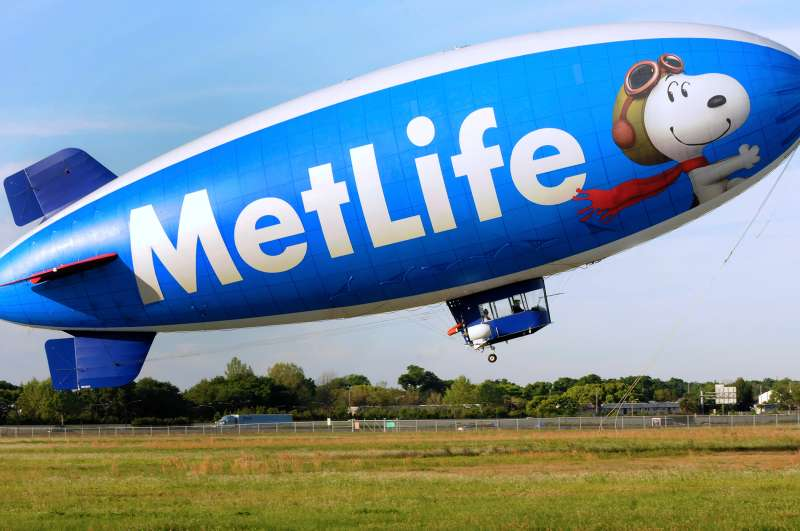 Snoopy One , a 128 foot long blimp, begins its ascent for an excursion at the Orlando Executive Airport, March 28, 2015, in Orlando, Florida. The airship was first launched in February 1994 and is one of two brand ambassadors for the Metropolitan Life Insurance Company (MetLife) in the United States. The helium-filled blimp is one of 12 airships owned and operated by the Van Wagner Airship Group. Snoopy One bears the MetLife logo as well as images of the Peanuts comic strip characters, Charlie Brown and Snoopy, and an advertisement for the Peanuts Movie, a computer-animated 3D film scheduled for release in November 2015. The blimp flies five days a week providing television coverage of sporting events, doing flyovers, and making special appearances.