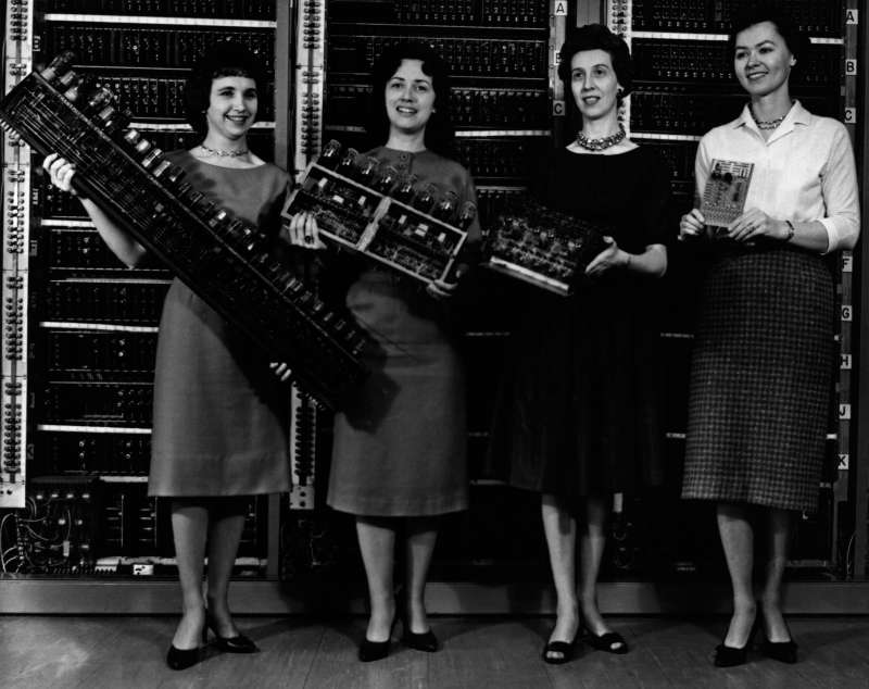 Women holding the first four computer circuit boards. From left to right: Mrs. Patsy Simmers with the ENIAC (Electronic Numerical Integrator And Computer) board; Mrs. Gail Taylor, with the EDVAC (Electronic Discrete Variable Automatic Computer) board; Mrs.