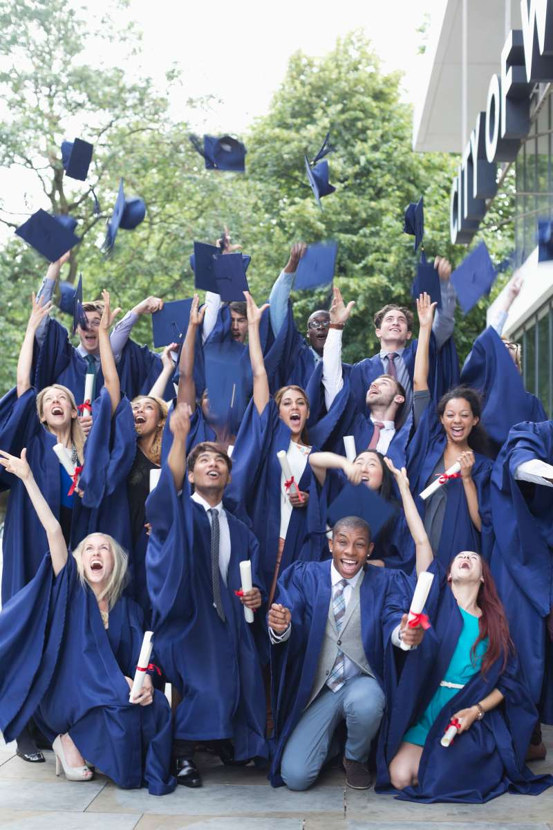 Group portrait of students in graduation gowns throwing mortarboards in the air