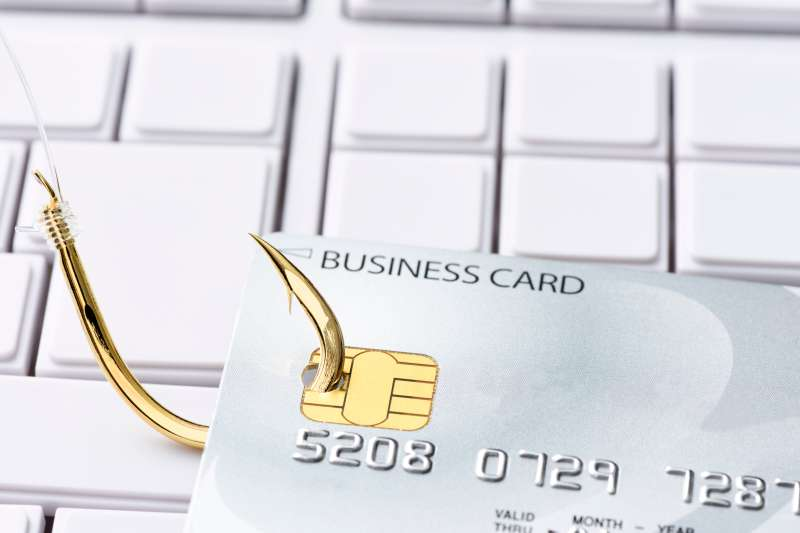 Close-up of credit card with fishing hook on computer keyboard