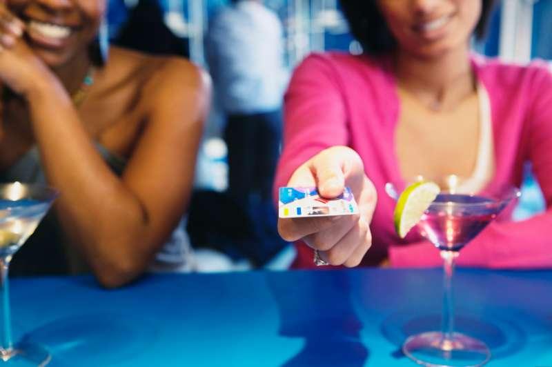 African woman handing credit card over bar