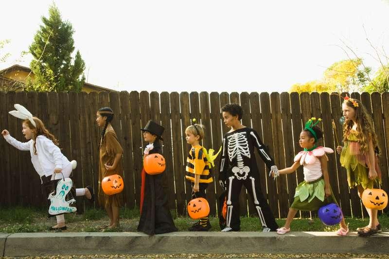 Children in Halloween costumes holding hands