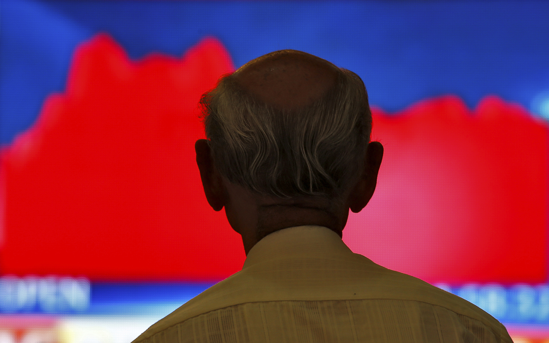 A man looks at a screen displaying news of markets update inside the Bombay Stock Exchange (BSE) building in Mumbai, India, November 9, 2016.