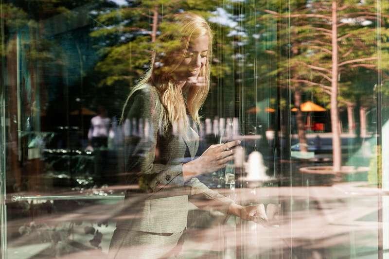 Business woman going through glass revolving door.