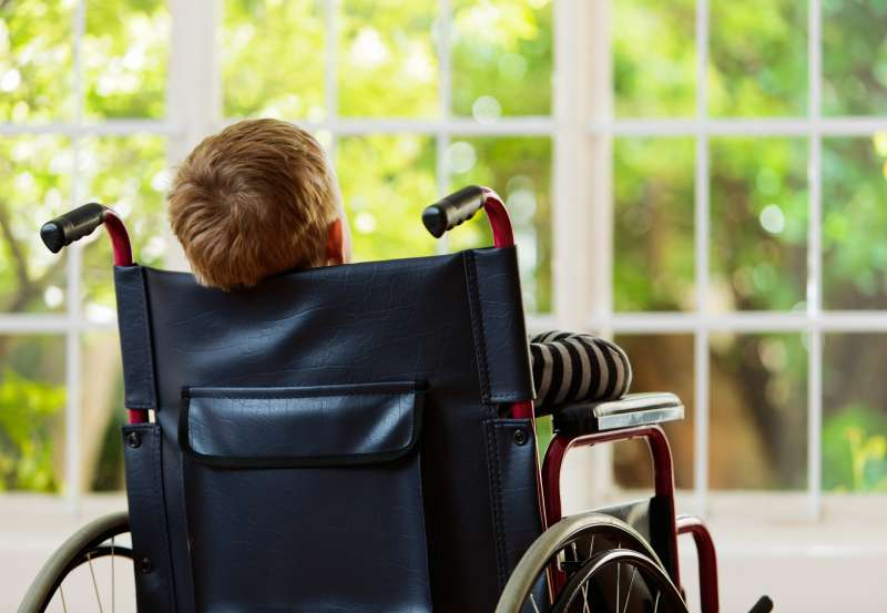 Backview of wheelchair-bound boy watching garden he cannot play in
