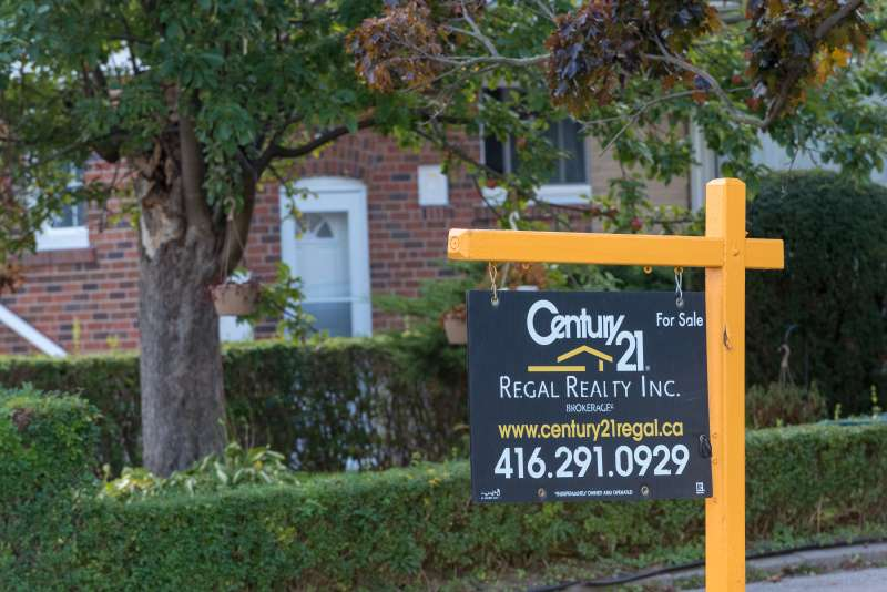 Housing Market: Century 21 realtor board with a for-sale