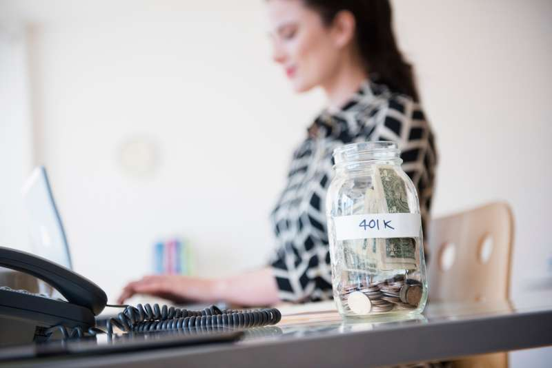401k money jar on desk of Caucasian businesswoman