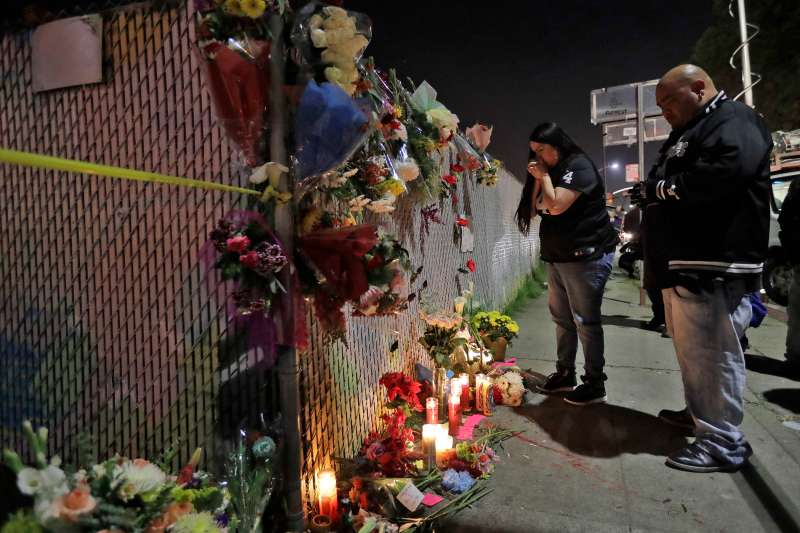 Sol Rodriguez, center, and Aaron Torres visit a shrine for the victims of a warehouse fire near the site Sunday, Dec. 4, 2016, in Oakland, Calif. The death toll was expected to rise, as crews using buckets and shovels slowly made their way through the building, finding victims where they least expected them, Alameda County Sheriff's Sgt. Ray Kelly said.