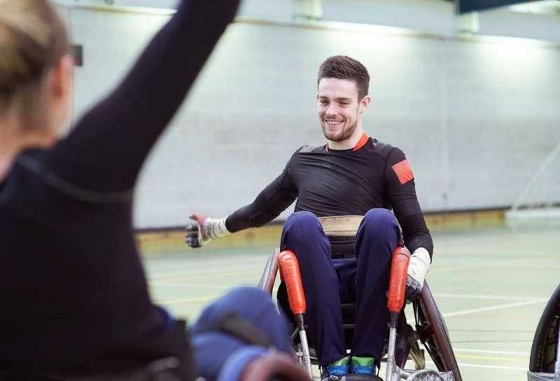 Paraplegic athlete stretching with female teammate