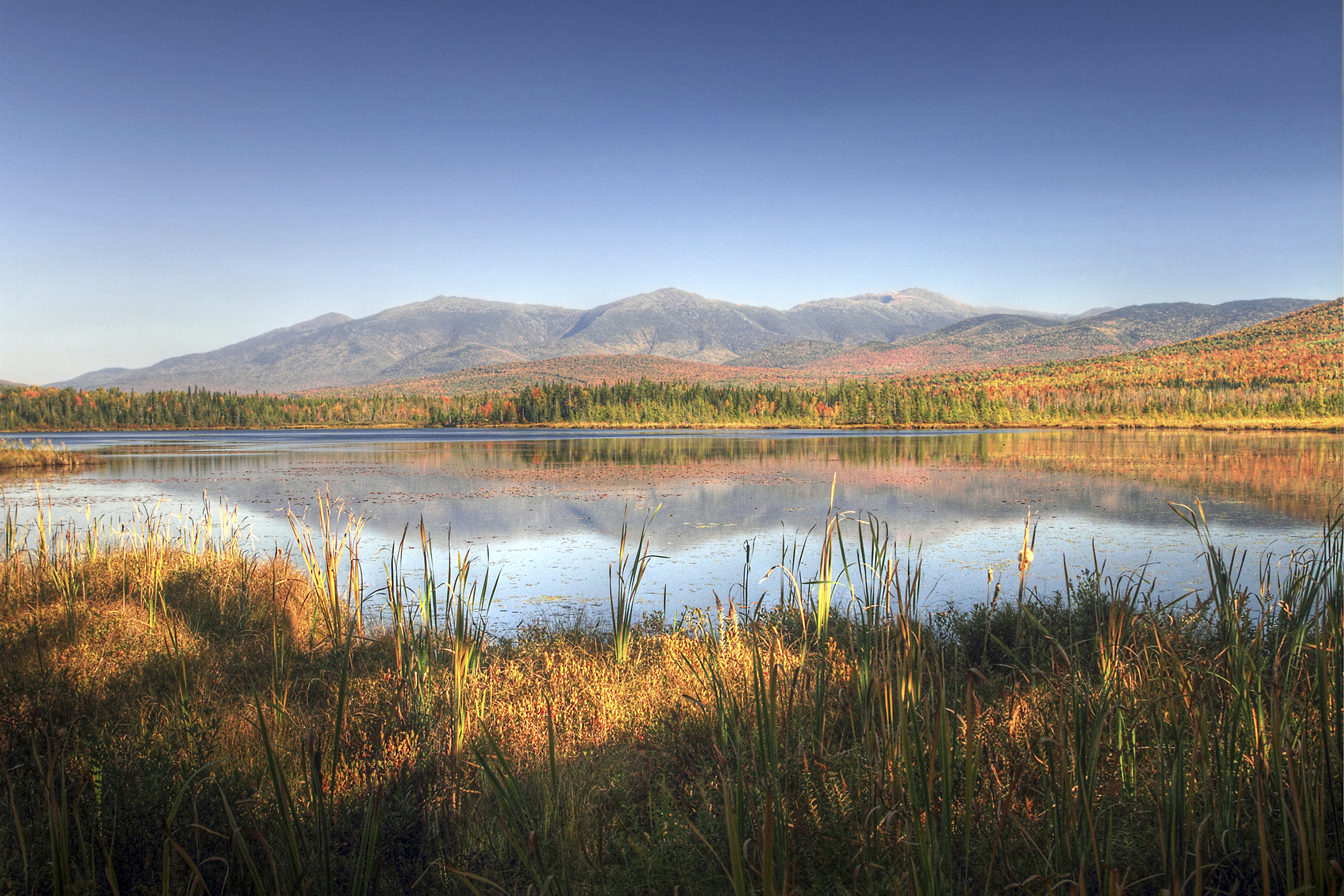 A view across Cherry Pond or Pondicherry with White Mountains Presidential range in background.