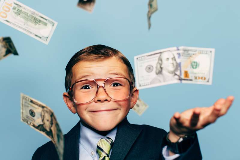 young boy in suit and glasses surrounded by falling money