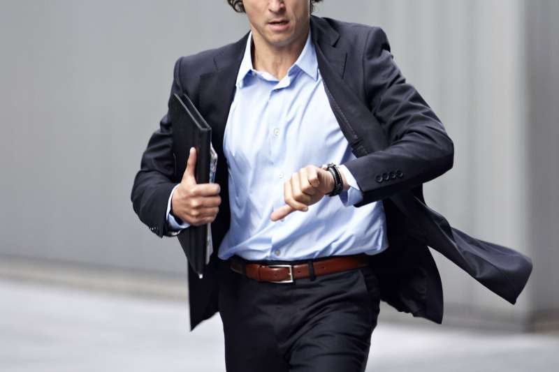 Man checking watch and running late