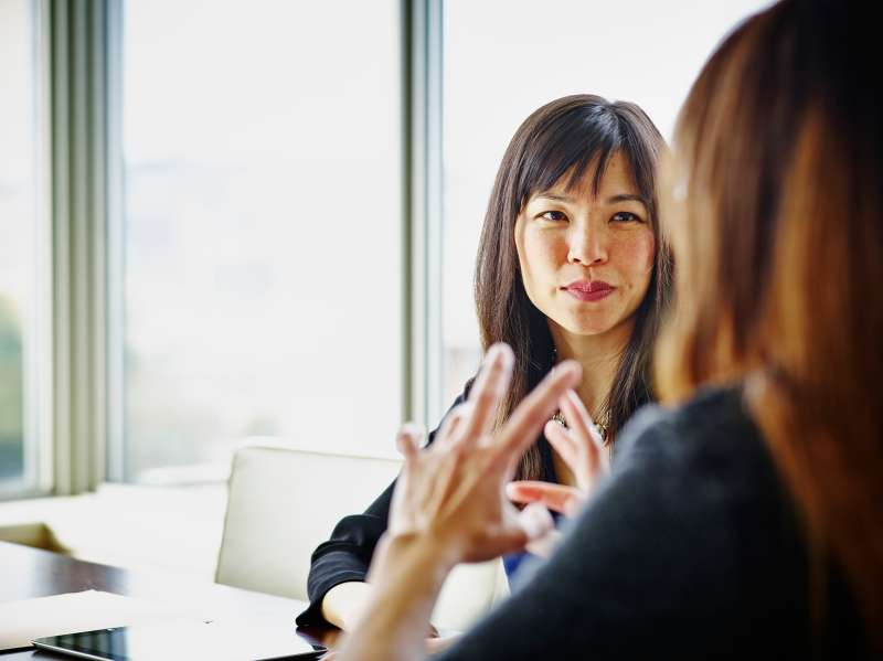 Two businesswomen discussing project details at table in conference room