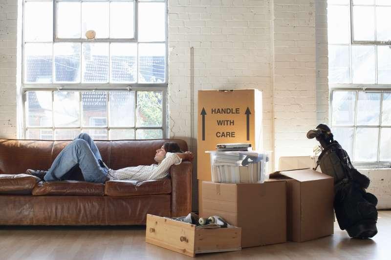 Young man lying down on sofa wearing headphones