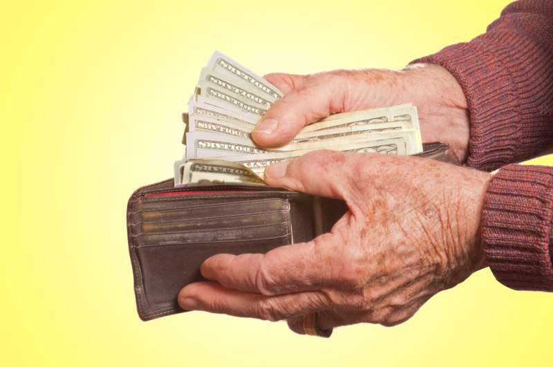 senior pulling money out of wallet