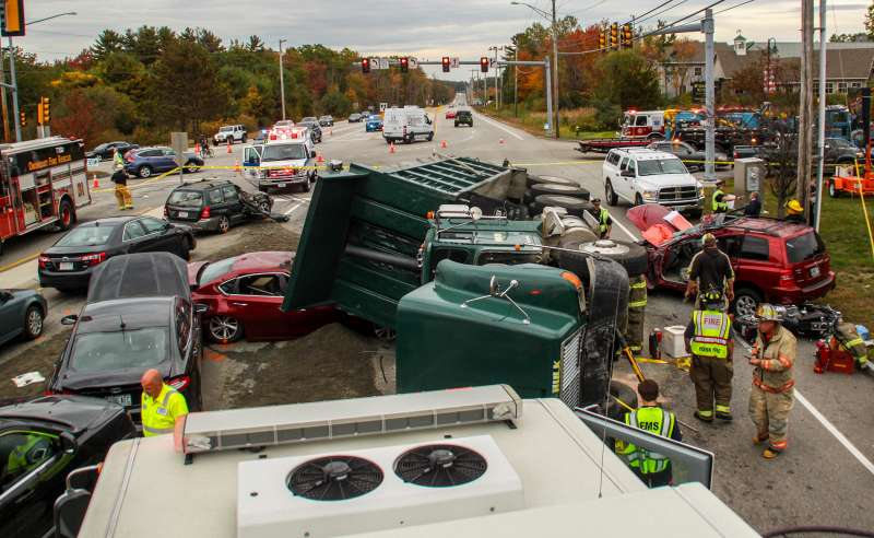 Emergency personnel investigate the scene of a 10-vehicle accident, Thursday, Oct. 13, 2016 in York, Maine. The accident happened when a dump truck filled with dirt tipped onto its side, demolishing a number of cars and sending multiple people to the hospital.