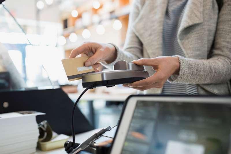Customer paying at credit card reader in market