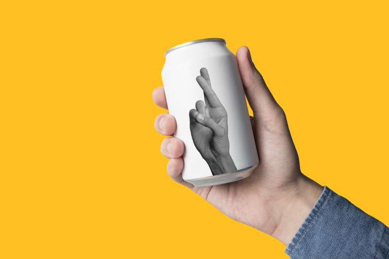 photo illustration of beer can with crossed fingers printed on it
