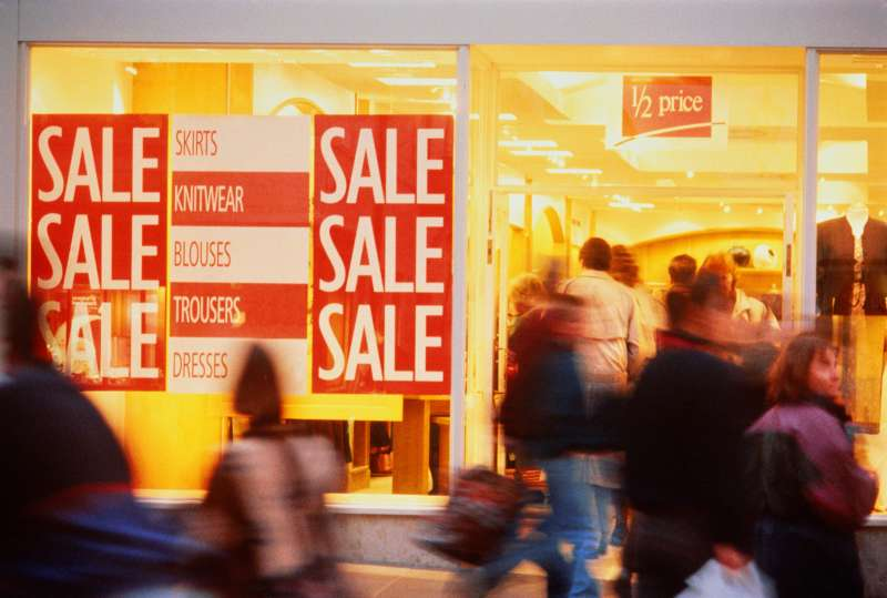 Shoppers entering store with sale signs displayed in window
