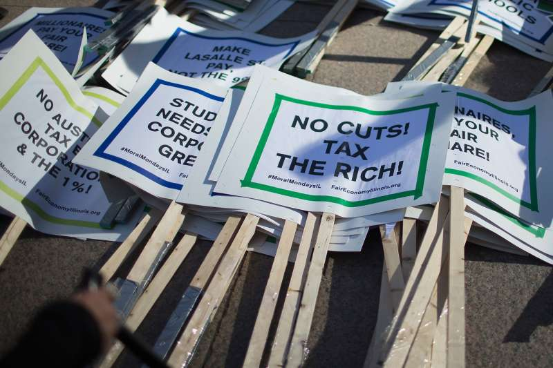 Signs sit in a pile before the start of a protest against the state of Illinois budget stalemate on November 2, 2015 in Chicago, Illinois.