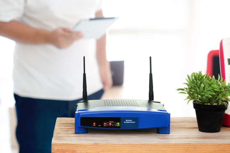 closeup of a wireless router and a young man using Tablet on living room at home