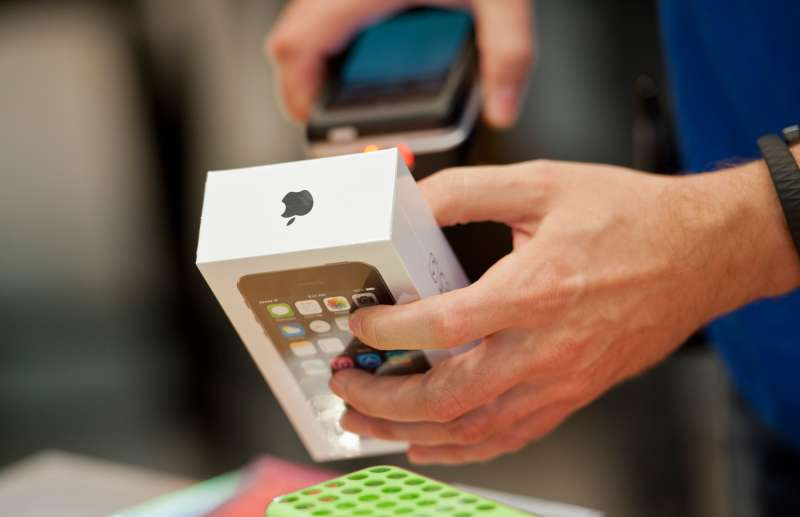 A sale person scans an Apple i-Phone 5s as sales start for the i-phone 5c and 5s in the Apple Store, on September 20, 2013 in Berlin, Germany.