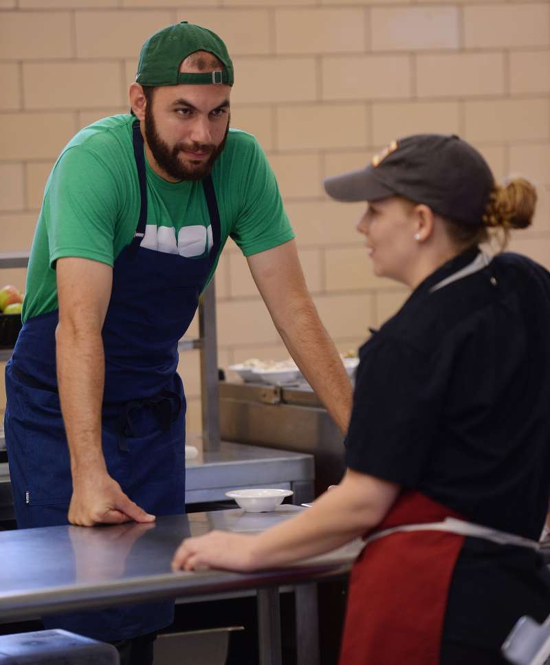 In this Sept. 23, 2016 photo, chef Daniel Giusti, left, chats with chef April Kindt between lunch waves at Bennie Dover Jackson Middle School in New London, Conn. The New London school district is in the midst of what's been called a food revolution following the hiring of two professional chefs. The Day reports students at Bennie Dover Jackson Middle School and New London High School are having meals that are something they say they've never seen the likes of in a school cafeteria.