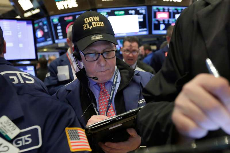 In this Wednesday, March 1, 2017, file photo, trader Richard Cohen wears a  Dow 21,000  cap as he works on the floor of the New York Stock Exchange. Excitement that President Donald Trump will drive business-friendly policies is only one of the reasons behind the stock market's recent surge.