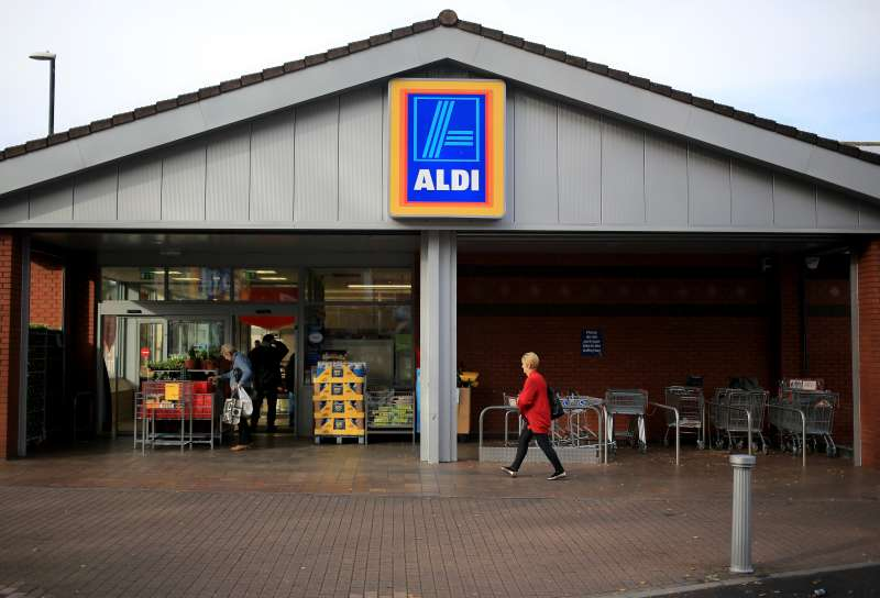 Shoppers enter a branch of the budget supermarket Aldi in Bristol, England.