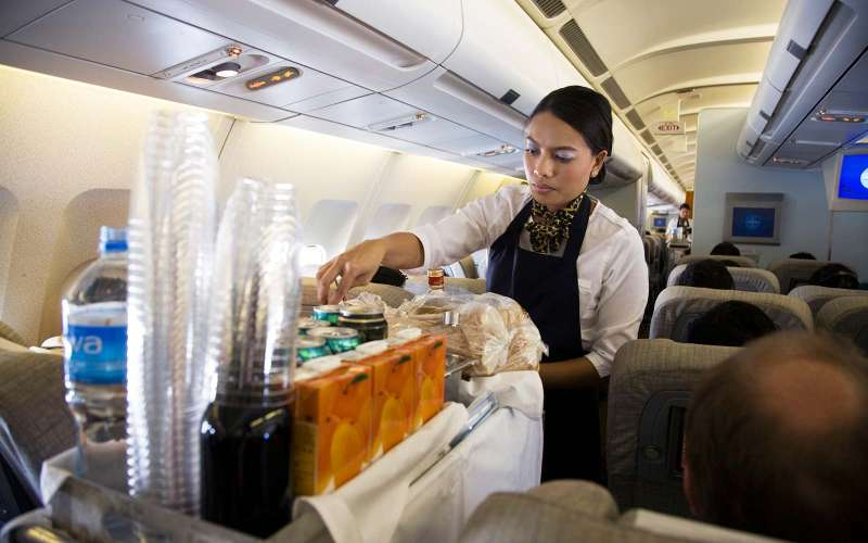 B79MG3 Cabin crew / air stewardess serves drinks to passengers from a trolley cart during a flight (45)