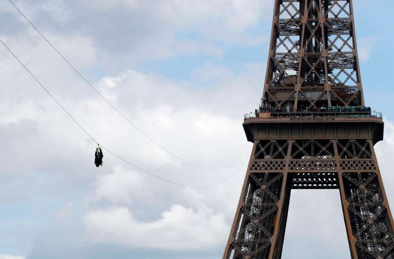 A person rides on a zip-line descending from the second floor of the Eiffel Tower to the Plateau Joffre on June 5, 2017 in Paris.