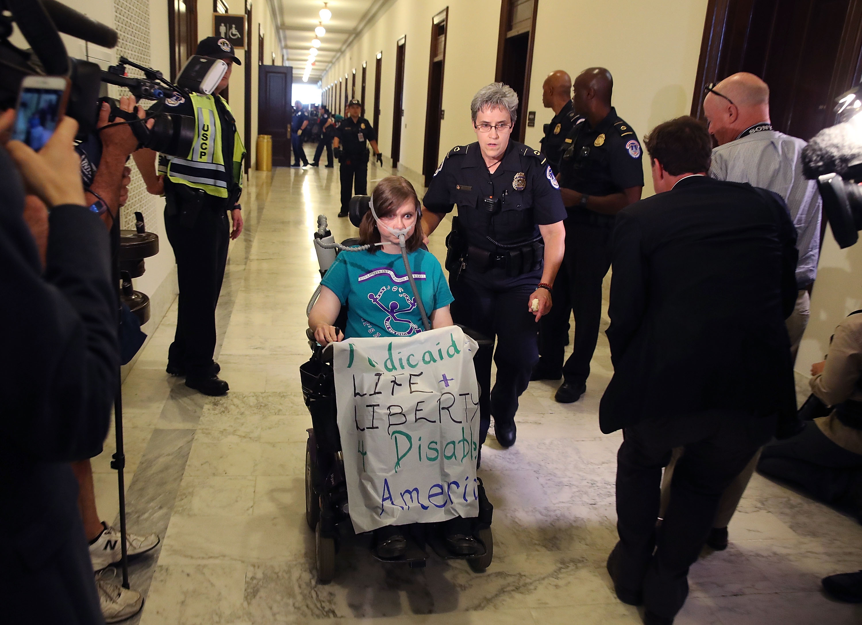 U.S. Capitol Police remove Laura Halvorson, a protester, from in front of the office of Senate Majority Leader Mitch McConnell (R-KY) inside the Russell Senate Office Building on Capitol Hill, on June 22, 2017 in Washington, DC.