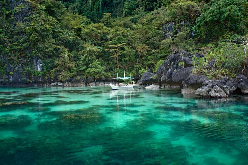 An outrigger canoe hidden in a lagoon among the islands of El Nido, enabling tourists on board to take a bath in the turquoise waters of Palawan archipelago.