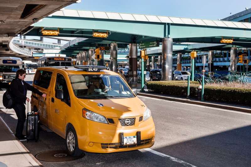 A taxi picking up a passenger outside LaGuardia Airport.