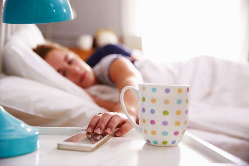 Woman in bed reaching for her mobile phone on nightstand