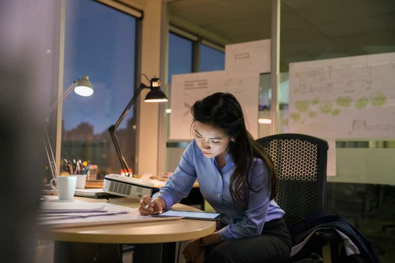 Businesswoman with digital tablet working late in office