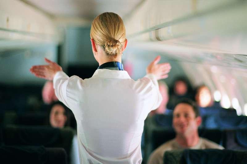 Rear View of Air Stewardess Explaining Aeroplane Safety to Passengers