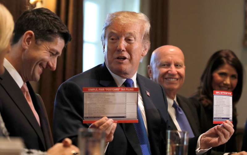 U.S. President Trump holds sample tax forms as he promotes tax plan at the White House in Washington