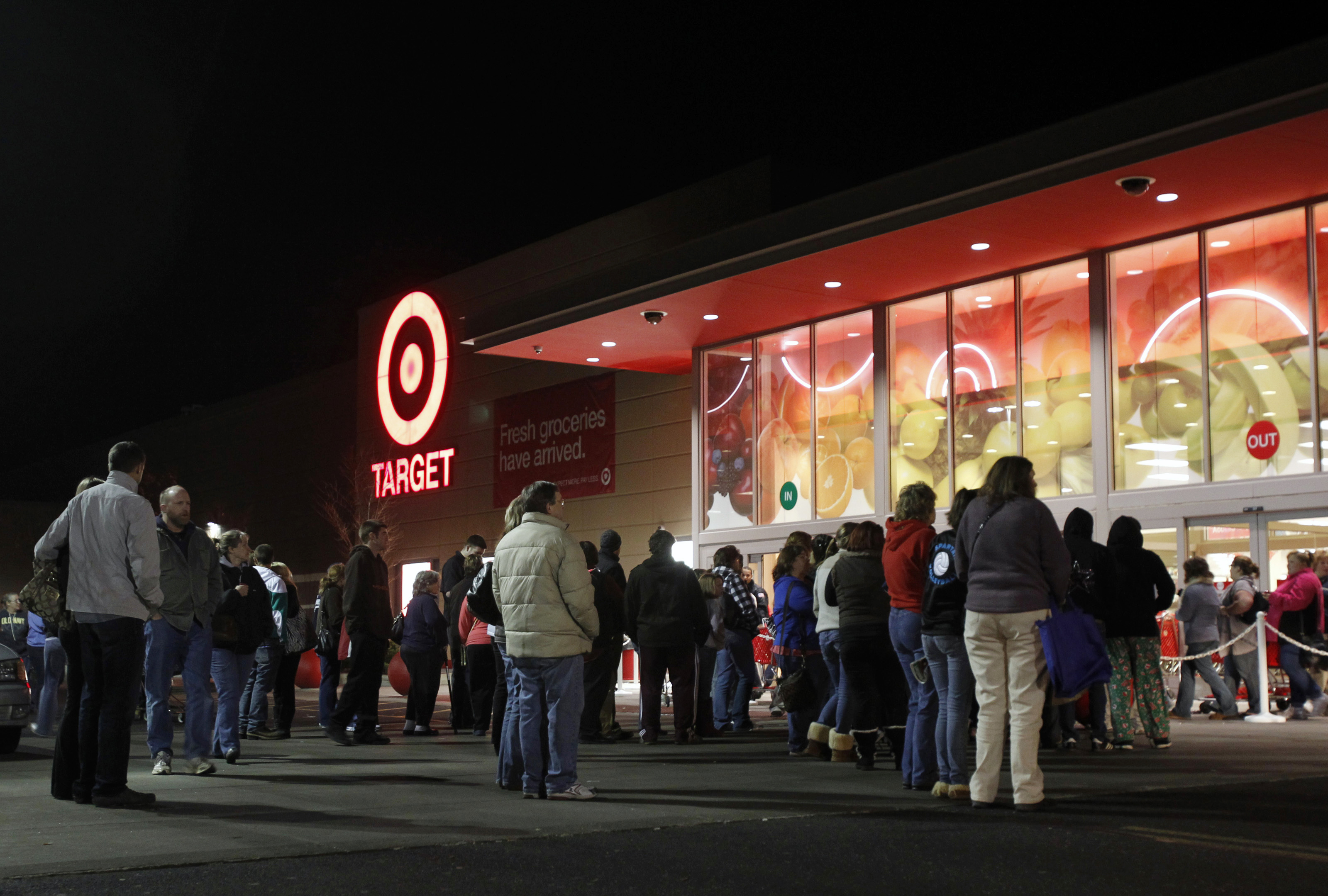 """Shoppers stand outside of a Target store at midnight on """"Black Friday"""" as they wait for those who stood in line to enter the store first in Torrington"""