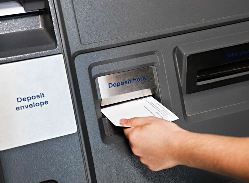 Hand places deposit envelope in  ATM slot