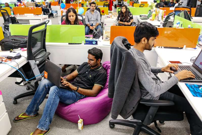 India's growth is a key long-term global trend to watch. Here, employees work on their laptops at Xiaomi Corp. headquarters in Bengaluru, India.