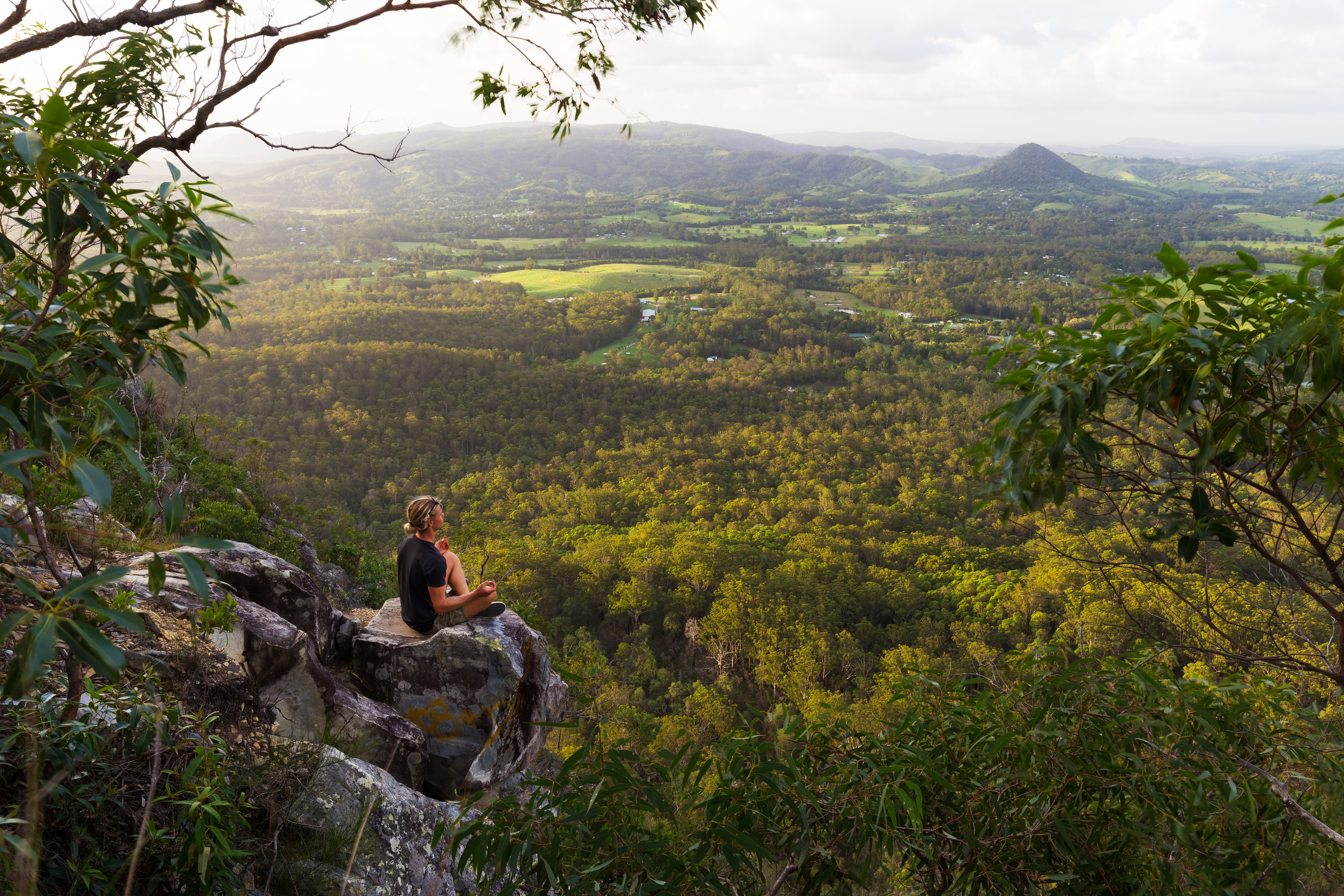 A young man meditates on top of a mountain with expansive views near Noosa Heads, Australia.