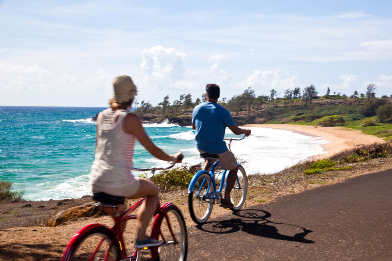 Couple ride on oceanside path. Kapaa Kauai County.
