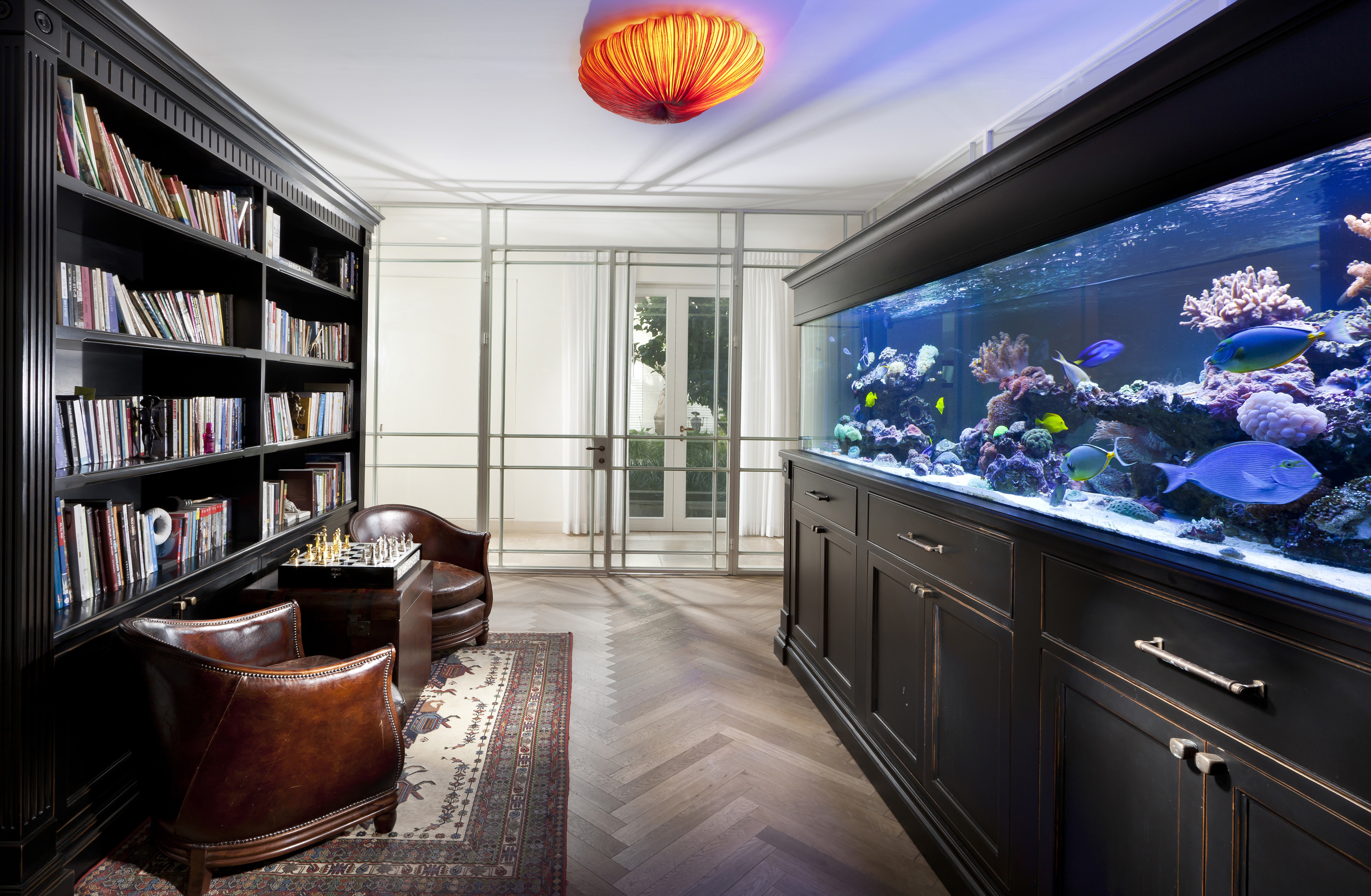 Room with large fish tank and bookcase, leather armchairs and chess set in country villa, Moshav Bnaya, Israel.