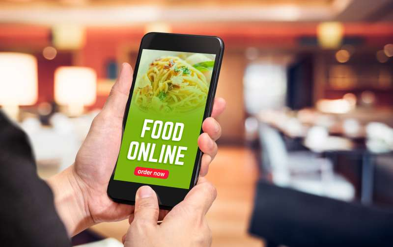Close up hand holding mobile phone with order food online word on screen with blur restaurant bokeh light background,online food marketing concept.
