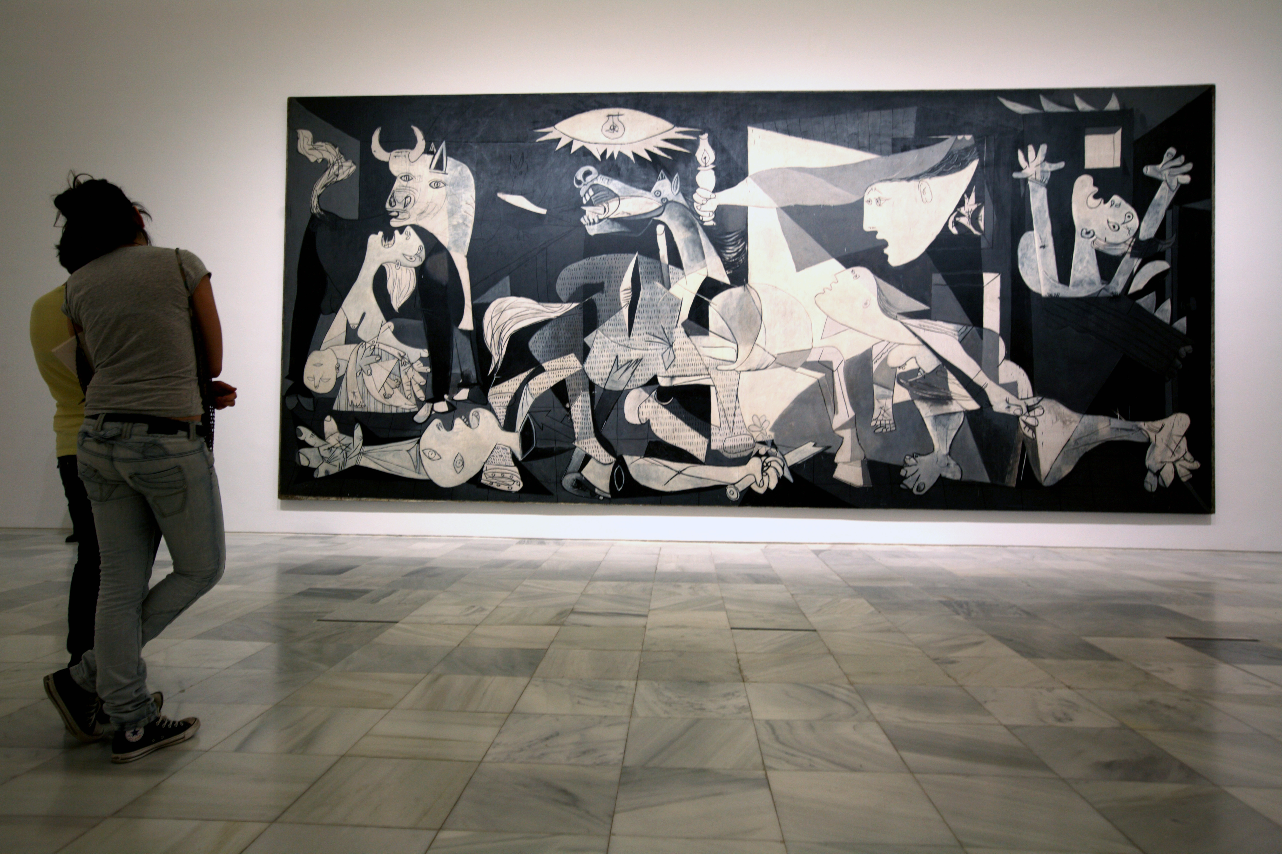 Visitors looking at Pablo Picasso's Guernica in Reina Sofia National Art Museum (Museo Nacional de Arte Reina Sofia).