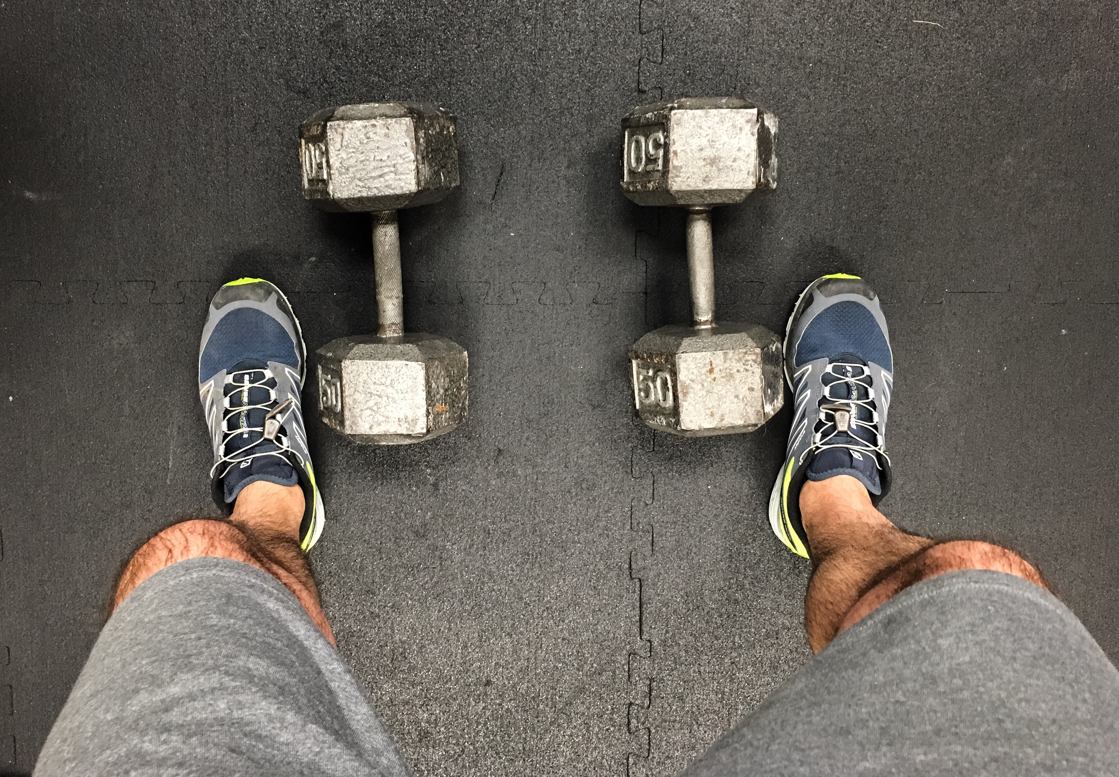 Low Section Of Man Standing By Dumbbells On Floor