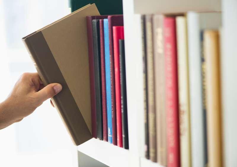 Hand choosing book from shelf