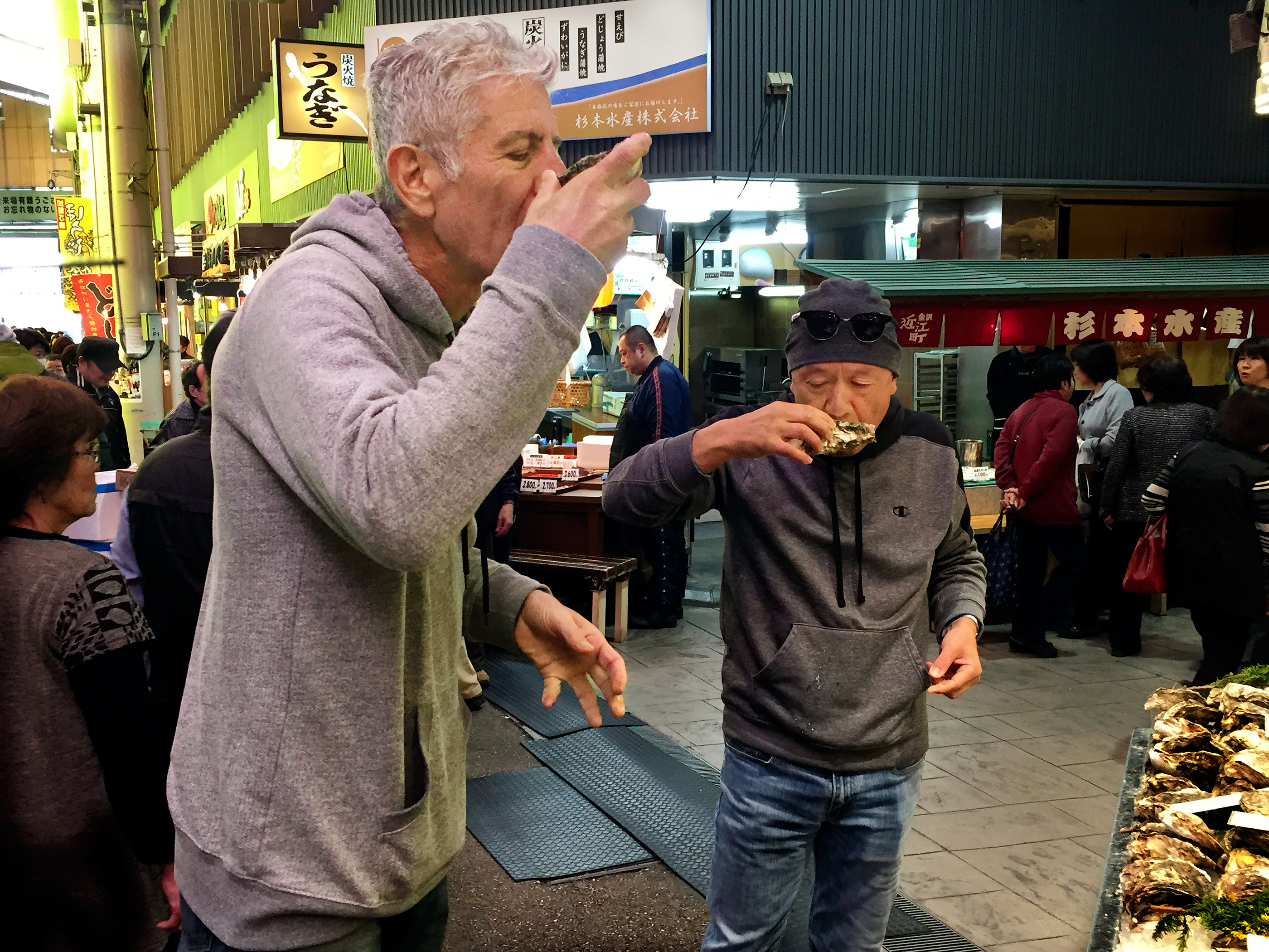 Anthony Bourdain and chef Masa Takayama sample oysters in the streets of Kanazawa, Japan.